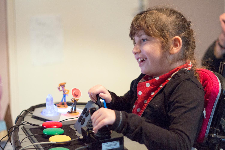 Smiling girl using adapted gaming controls