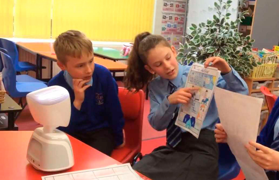 schoolchildren showing a robot a printed page