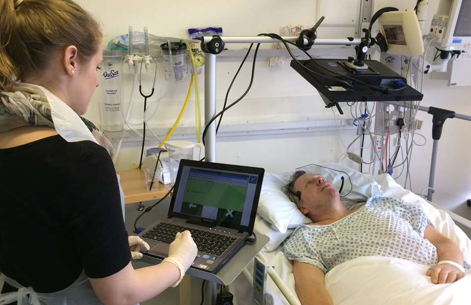 man lying in hospital bed looking at screen, woman with computer by bedside