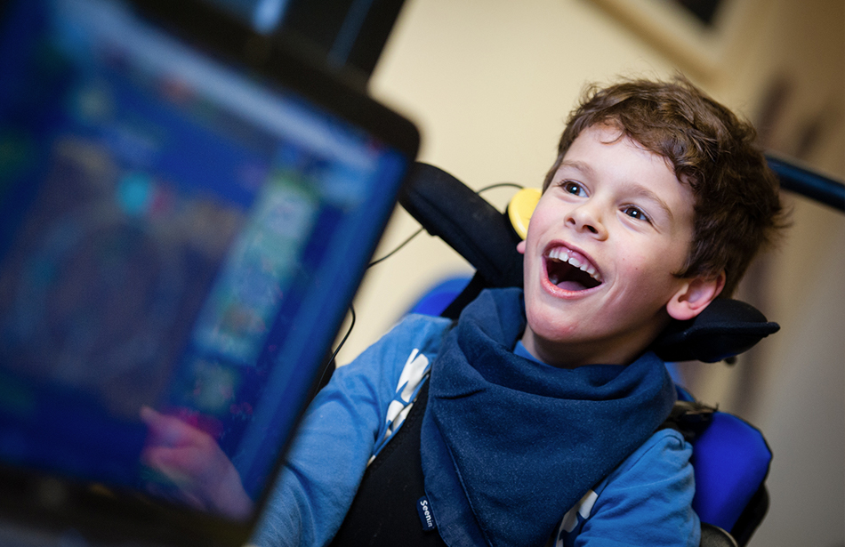 smiling boy with computer screen