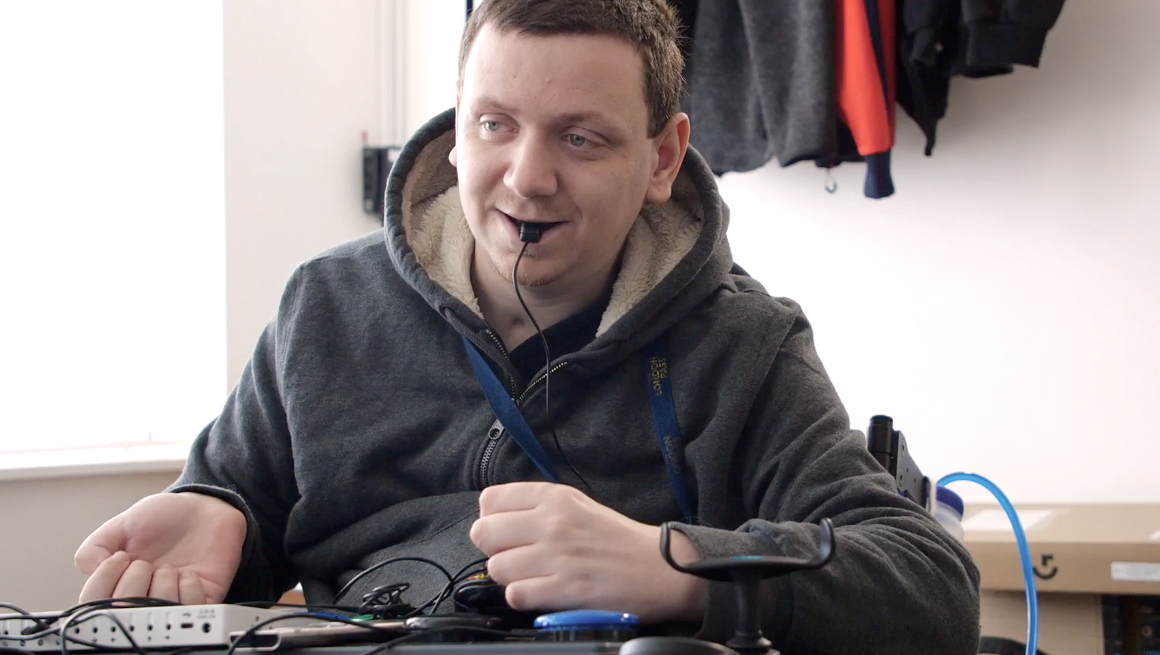 Seated man using adapted controls to play games