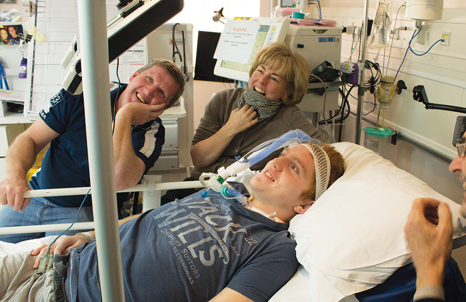 man lying in hospital bed using eye-controlled computer