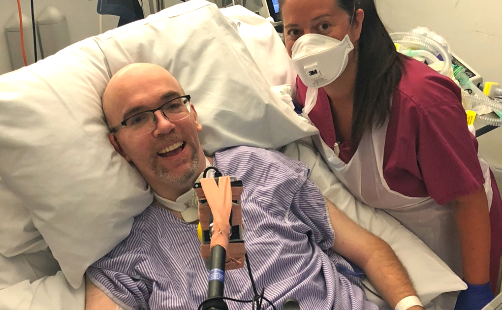 Smiling man in hospital bed with nursing sister standing