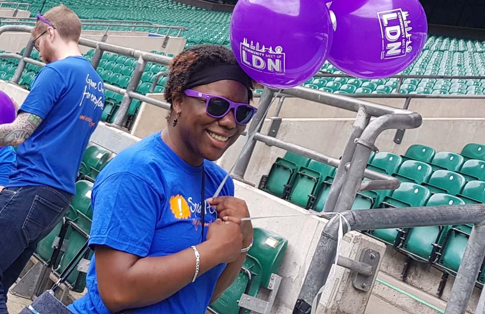 Woman in stadium holding balloons